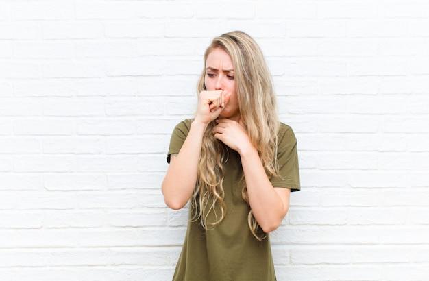 Giovane donna bionda sentirsi male con mal di gola e sintomi influenzali, tossendo con la bocca coperta contro il muro di mattoni Foto Premium