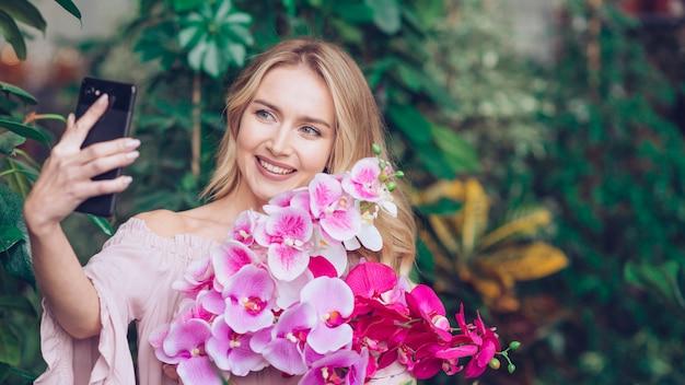 Giovane donna bionda sorridente che giudica orchidea fresca a disposizione che prende autoritratto dal telefono cellulare Foto Gratuite