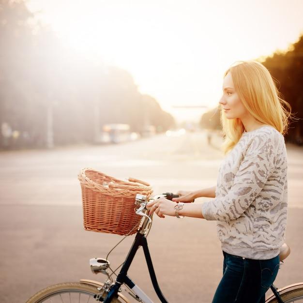 Giovane donna bionda su una bicicletta d'epoca Foto Premium