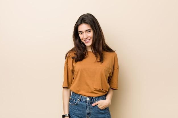 Giovane donna bruna controbeige felice, sorridente e allegra. Foto Premium