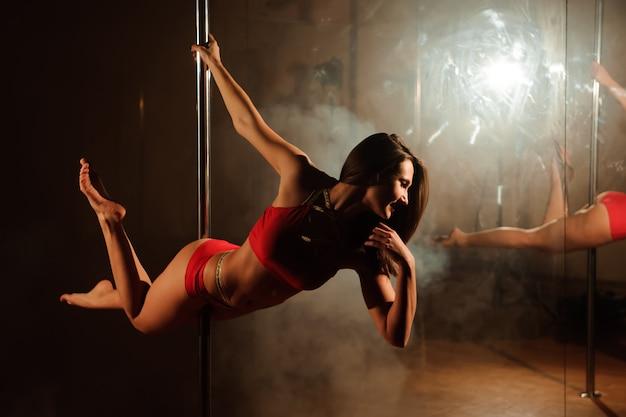 Giovane donna calda in lingerie sexy esegue sensuale pole dance. Foto Premium