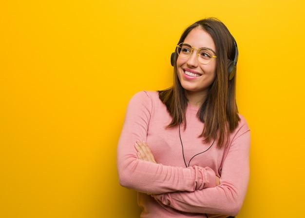Giovane donna carina ascoltando musica sorridendo fiducioso e incrociando le braccia, alzando lo sguardo Foto Premium