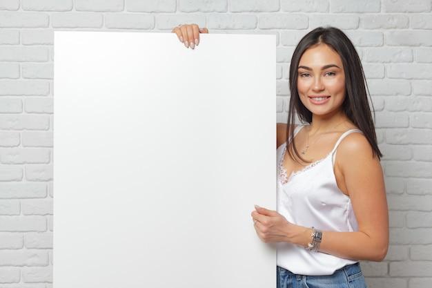 Giovane donna castana che tiene grande bordo bianco in bianco con lo spazio della copia Foto Premium