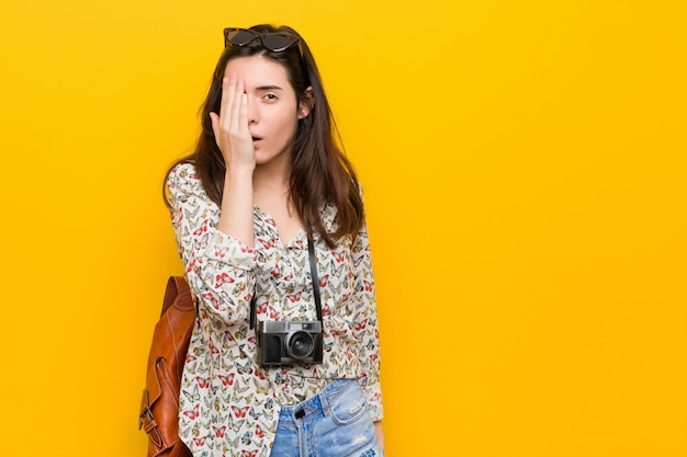 Giovane donna castana del viaggiatore divertendosi coprendo metà del viso con la palma. Foto Premium