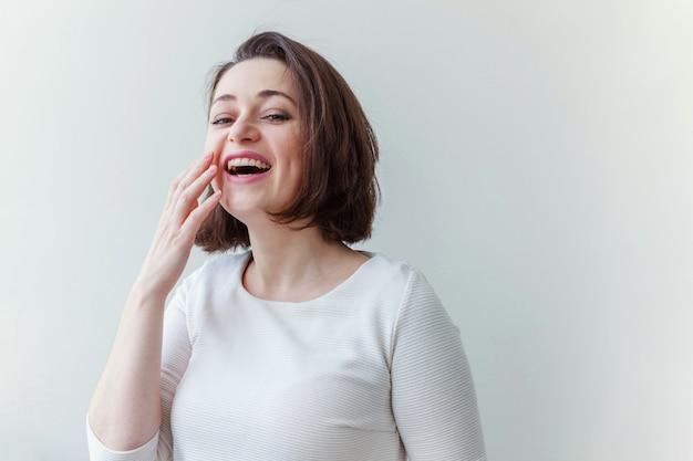 Giovane donna castana positiva felice del ritratto di bellezza su bianco isolata Foto Premium