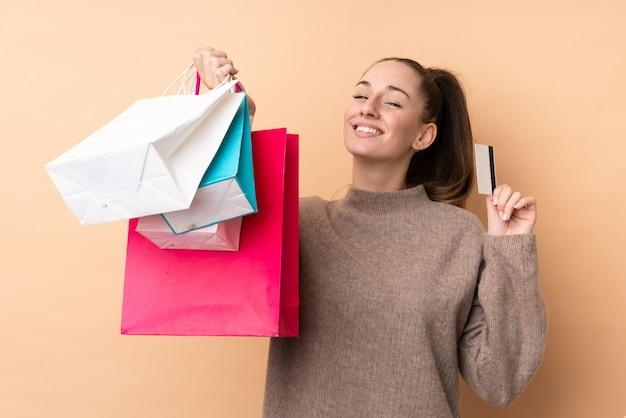 Giovane donna castana sopra i sacchetti della spesa isolati della tenuta della parete e una carta di credito Foto Premium