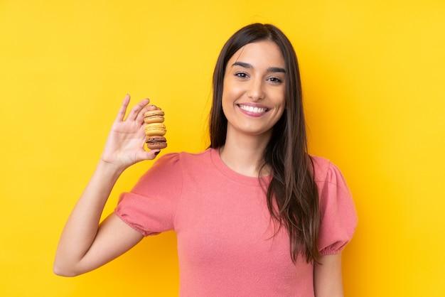 Giovane donna castana sopra la parete gialla isolata che tiene i macarons francesi variopinti e che sorride molto Foto Premium