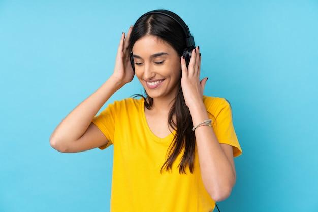 Giovane donna castana sopra musica d'ascolto isolata della parete blu Foto Premium