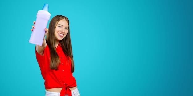 Giovane donna casuale che tiene una bottiglia di un detersivo liquido Foto Premium