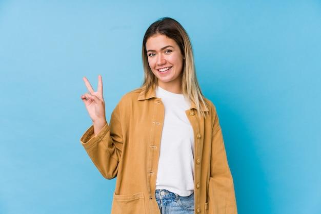 Giovane donna caucasica allegra e spensierata che mostra un simbolo di pace con le dita. Foto Premium