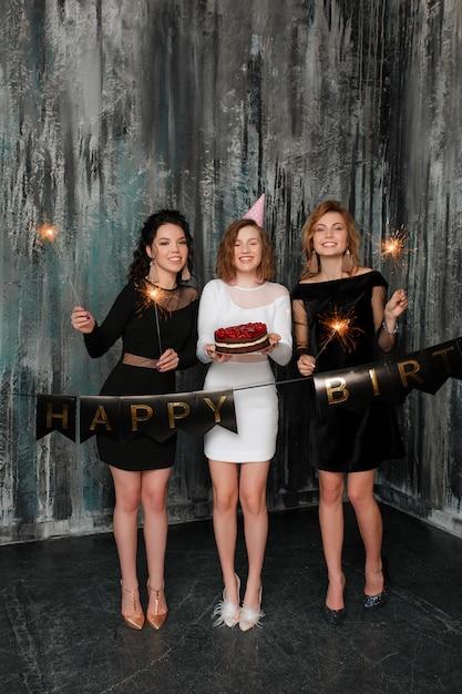 Giovane donna caucasica attraente con una torta di compleanno tra i suoi amici Foto Gratuite