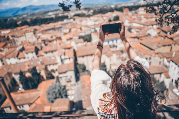 Giovane donna caucasica che fa foto dal telefono cellulare dal posto di osservazione Foto Premium