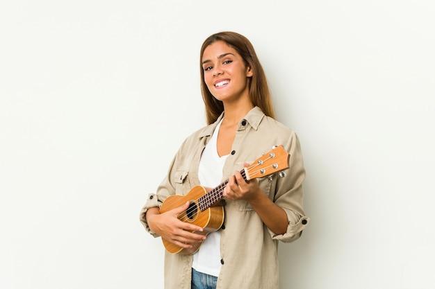 Giovane donna caucasica che gioca ukelele isolato Foto Premium