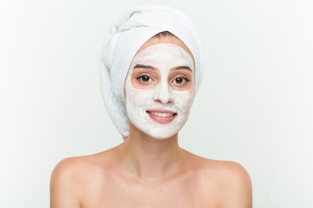 Giovane donna caucasica che gode del trattamento maschera offaciale Foto Premium