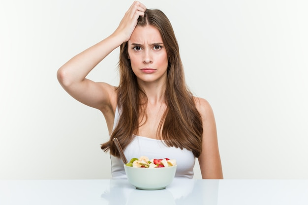 Giovane donna caucasica che mangia la ciotola di frutta che è scossa, ricorda un incontro importante. Foto Premium