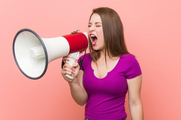 Giovane donna caucasica che parla tramite un megafono Foto Premium