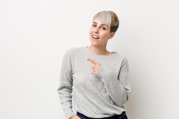 Giovane donna caucasica curvy che sorride e che indica da parte, mostrando qualcosa allo spazio. Foto Premium