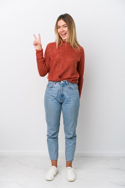 Giovane donna caucasica dell'ente completo allegra e spensierata che mostra un simbolo di pace con le dita. Foto Premium