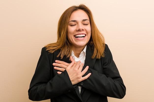 Giovane donna caucasica di affari che ride mantenendo le sue mani sul cuore Foto Premium