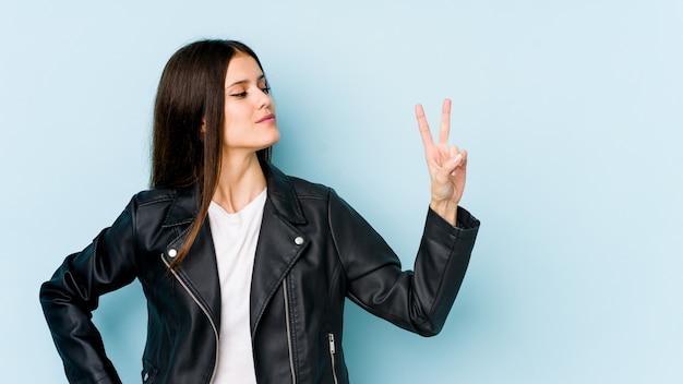 Giovane donna caucasica isolata sulla parete blu allegra e spensierata che mostra un simbolo di pace con le dita. Foto Premium