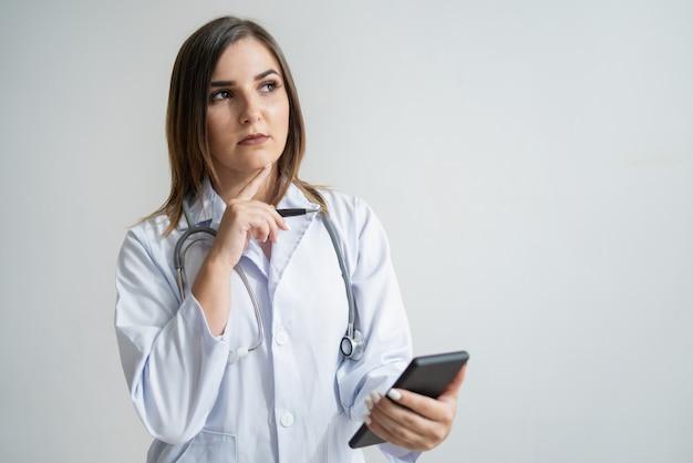 Giovane donna caucasica pensierosa nel telefono della tenuta del cappotto del laboratorio Foto Gratuite