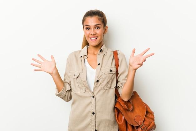 Giovane donna caucasica pronta per un viaggio che riceve una piacevole sorpresa, eccitata e alzando le mani. Foto Premium