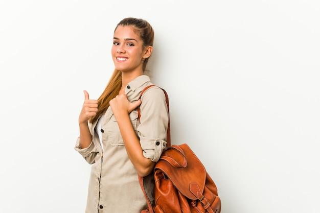 Giovane donna caucasica pronta per un viaggio che sorride e che alza pollice in su Foto Premium
