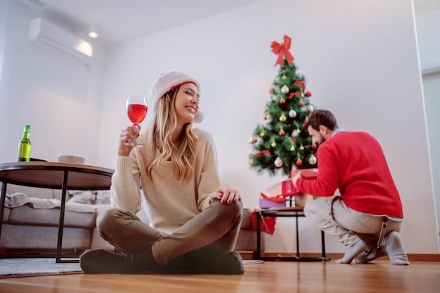 Giovane donna caucasica sorridente attraente con il cappello di santa sulla testa che si siede sul pavimento e che beve vino. sullo sfondo il suo ragazzo mette regali sotto l'albero. concetto di vacanze di natale. Foto Premium