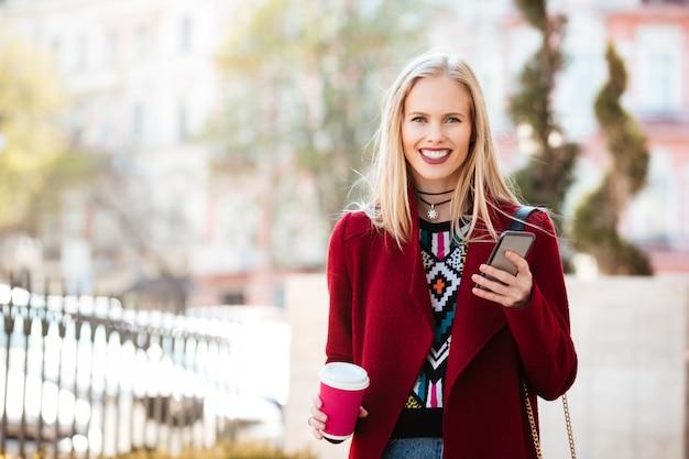 Giovane donna caucasica sorridente che cammina all'aperto che chiacchiera Foto Gratuite