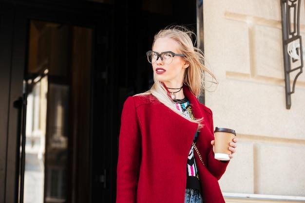 Giovane donna caucasica stupefacente che cammina all'aperto bevendo caffè. Foto Gratuite