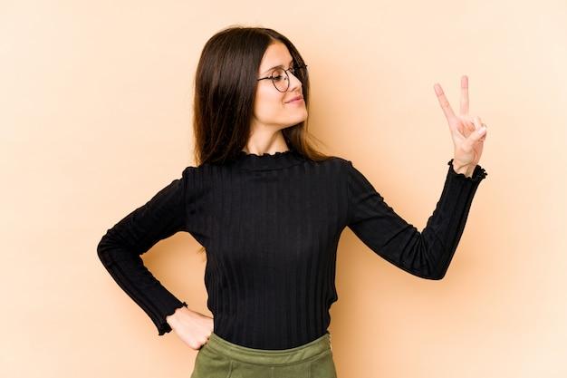 Giovane donna caucasica sulla parete beige gioiosa e spensierata mostrando un simbolo di pace con le dita. Foto Premium