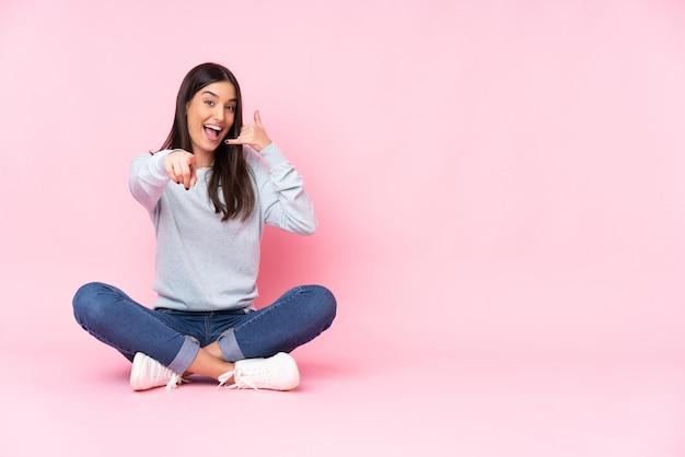 Giovane donna caucasica sulla parete rosa che fa gesto del telefono e che indica parte anteriore Foto Premium