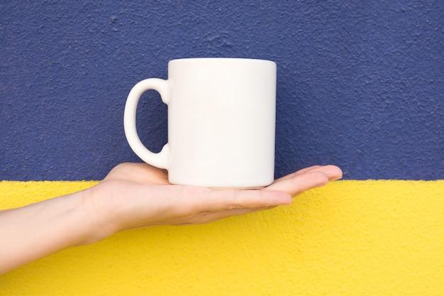 Giovane donna caucasica tiene in mano palm blank mockup tazza bianca su duotone giallo scuro parete dipinta di blu Foto Premium