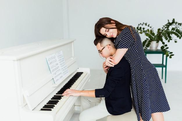 Giovane donna che abbraccia il suo ragazzo da dietro a suonare il pianoforte Foto Gratuite