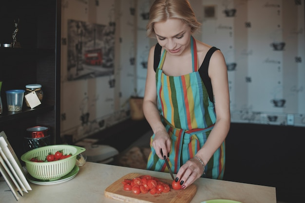 Giovane donna che affetta i pomodori Foto Gratuite