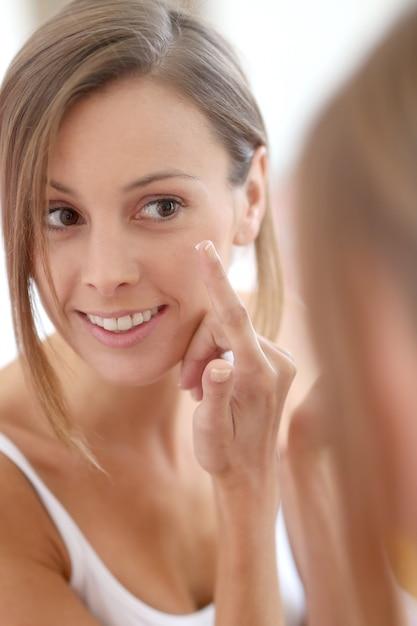 Giovane donna che applica la crema anti-rughe Foto Premium