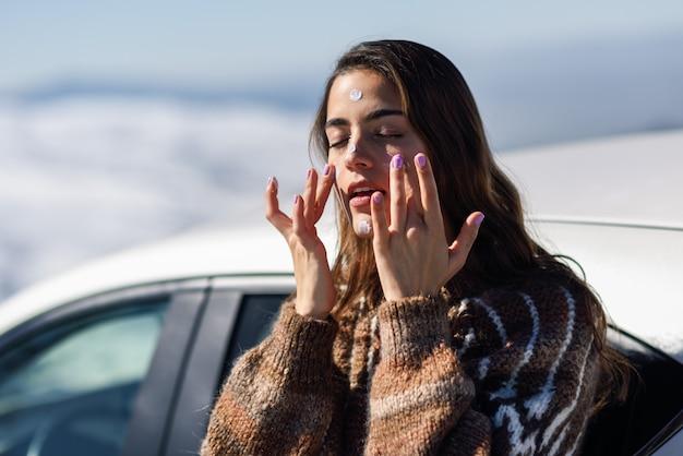 Giovane donna che applica protezione solare sul suo fronte nel paesaggio della neve Foto Premium
