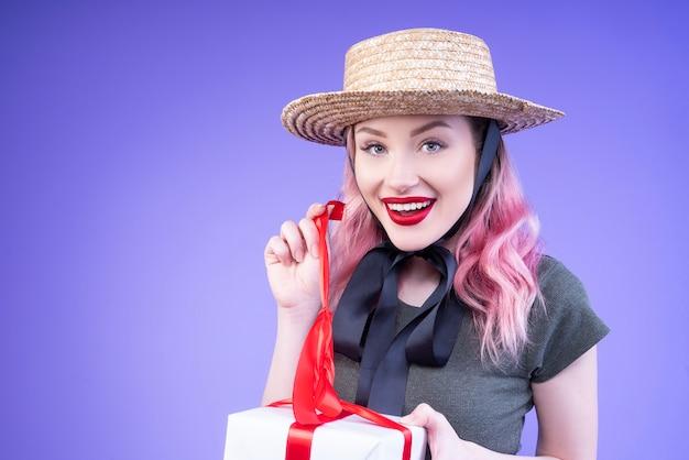 Giovane donna che apre il suo regalo decorato con un nastro rosso Foto Gratuite