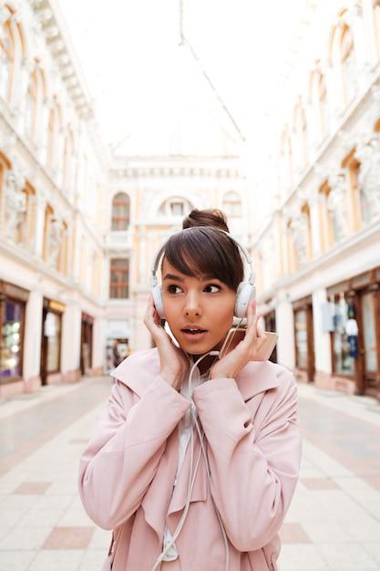 Giovane donna che ascolta la musica con le cuffie e che distoglie lo sguardo all'aperto Foto Gratuite