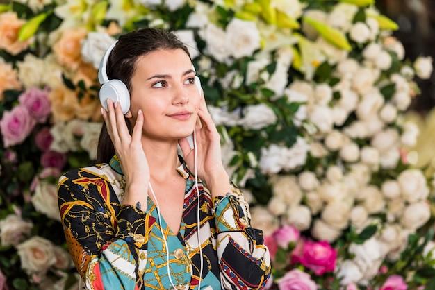 Giovane donna che ascolta la musica in serra Foto Gratuite