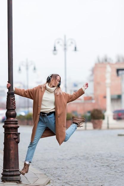 Giovane donna che ascolta la musica sulle cuffie nella città con lo spazio della copia Foto Gratuite