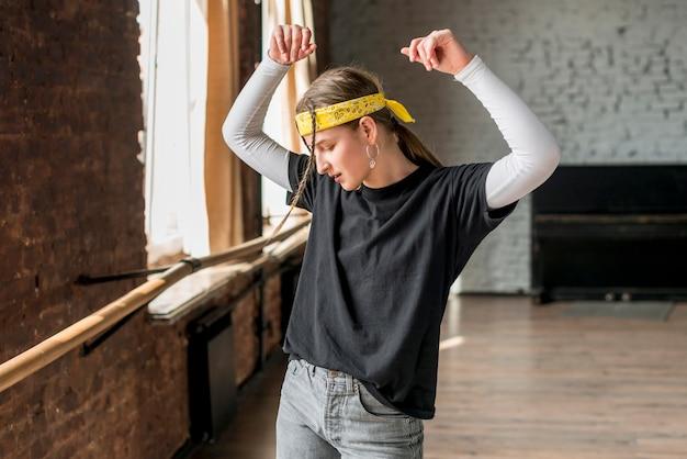 Giovane donna che balla in studio di danza Foto Gratuite