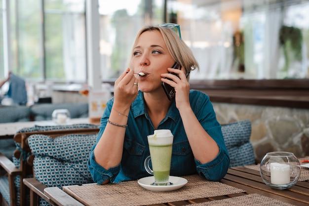 Giovane donna che beve godendo del latte del tè verde di matcha nella mattina di estate in caffè. Foto Premium