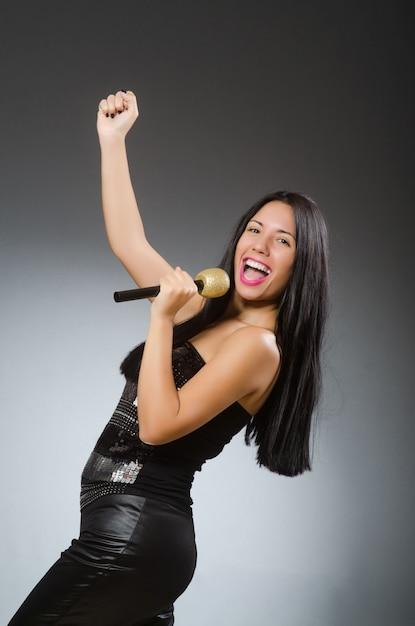 Giovane donna che canta nel club di karaoke Foto Premium