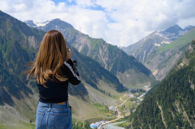 Giovane donna che cattura foto della montagna Foto Premium