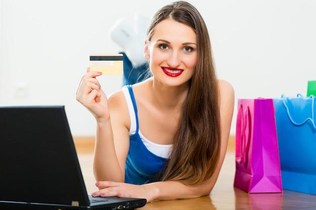 Giovane donna che compra in internet Foto Premium