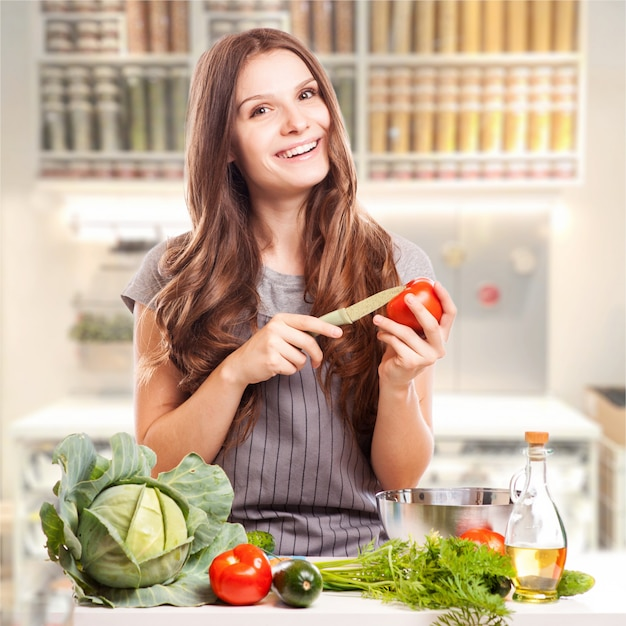 Giovane donna che cucina in cucina. cibo sano - insalata di verdure. dieta. concetto di dieta. uno stile di vita sano. Foto Premium