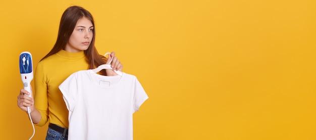Giovane donna che cuoce a vapore i suoi vestiti a casa, tenendo ferro da stiro a vapore e maglietta bianca sui ganci in mano, guardando da parte con sguardo serio, in posa contro il muro giallo. Foto Premium