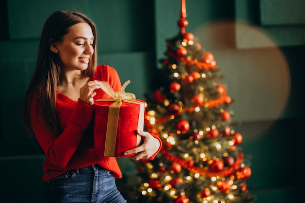 Giovane donna che disimballa regalo di natale dall'albero di natale Foto Gratuite