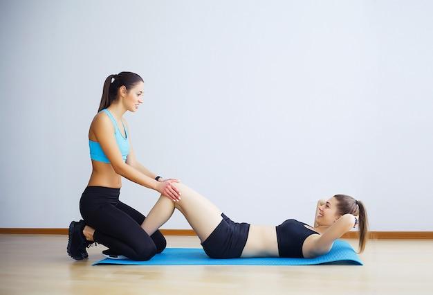 Giovane donna che esercita sit-up con assistenza di un'amica in palestra. Foto Premium